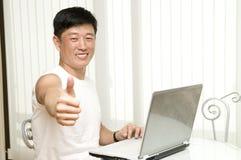 Der junge erfolgreiche Mann mit dem Computer sitzt Lizenzfreie Stockbilder
