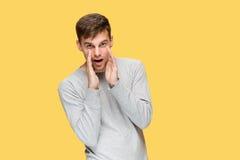 Der junge ernste Mann, der vorsichtig schauen und sprechendes Geheimnis stockbild