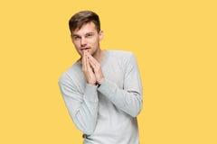 Der junge ernste Mann, der vorsichtig schauen und sprechendes Geheimnis lizenzfreies stockbild