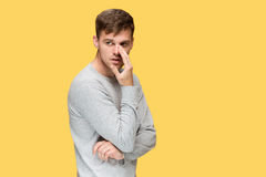 Der junge ernste Mann, der vorsichtig schauen und sprechendes Geheimnis stockbilder