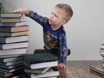 Der Junge erreicht für den Stapel von Büchern Lizenzfreies Stockfoto