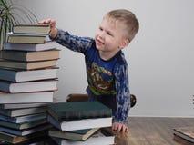 Der Junge erreicht für den Stapel von Büchern Lizenzfreie Stockfotografie