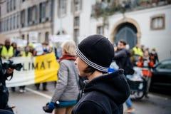 Der junge Erwachsene, der Marken betrachtet, gießen Marsch Le Climat, auf Franc sich zu schützen lizenzfreie stockbilder