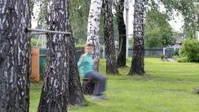 Der Junge fährt auf ein Schwingen unter den Birken stock video footage