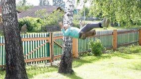 Der Junge fährt auf ein Schwingen unter den Birken stock footage