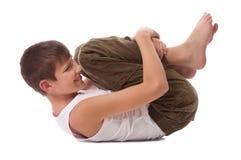 Der Junge führt gymnastische Übung durch Stockfoto