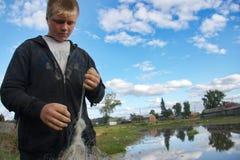 Der junge Fischer mit Netzen Stockbilder