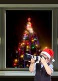 Der Junge fotografiert auf dem Hintergrund des Weihnachtsbaums außerhalb des Fensters Stockfotografie