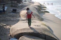 Der Junge geht durch eine enorme Tasche des Sandes Stockbilder