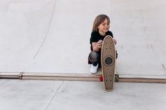 Der Junge gekleidet in der zuf?lligen Kleidung mit Skateboard in seinen Handst?nden in einem Rochenpark nahe bei dem Dia am sonni lizenzfreie stockbilder