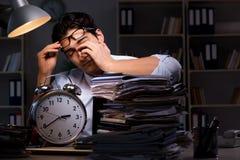 Der junge Geschäftsmann über die Zeit hinaus, der spät im Büro arbeitet Stockfotos