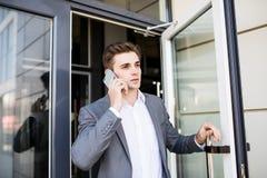 Der junge Geschäftsmann, der die Bürotür hält und erhalten Außenseitenweiß sprechen am Telefon Stockbilder