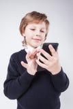 Der junge Geschäftsmann, der die Telefonanzeige betrachtet, schreibt und SMI Lizenzfreie Stockbilder