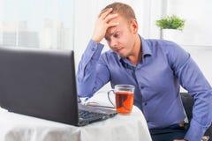 Der junge Geschäftsmann, der im Büro, sehr beteiligt arbeitet, löst Problem und gelehnten Kopf auf seiner Hand Lizenzfreie Stockfotografie