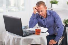 Der junge Geschäftsmann, der im Büro, sehr beteiligt arbeitet, löst Problem und gelehnten Kopf auf seiner Hand Stockfotografie