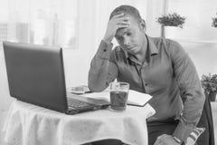 Der junge Geschäftsmann, der im Büro, sehr beteiligt arbeitet, löst Problem und gelehnten Kopf auf seiner Hand Stockbilder