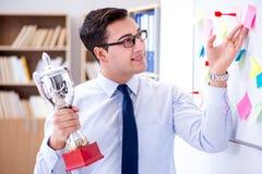 Der junge Geschäftsmann, der prize Schale im Büro empfängt Stockbild