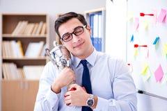 Der junge Geschäftsmann, der prize Schale im Büro empfängt Stockfoto