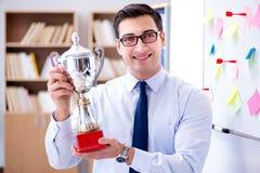 Der junge Geschäftsmann, der prize Schale im Büro empfängt Lizenzfreies Stockbild