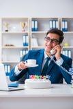 Der junge Geschäftsmann, der Geburtstag allein im Büro feiert Stockbild