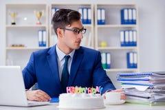Der junge Geschäftsmann, der Geburtstag allein im Büro feiert Lizenzfreie Stockbilder