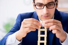 Der junge Geschäftsmanngebäude-Dominoturm im Büro lizenzfreies stockfoto