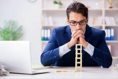 Der junge Geschäftsmanngebäude-Dominoturm im Büro stockbild