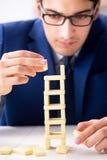 Der junge Geschäftsmanngebäude-Dominoturm im Büro lizenzfreie stockbilder