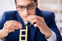 Der junge Geschäftsmanngebäude-Dominoturm im Büro stockfoto