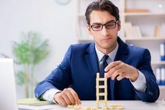 Der junge Geschäftsmanngebäude-Dominoturm im Büro lizenzfreies stockbild