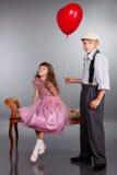 Der Junge gibt dem Mädchen einen roten Ballon Stockbild