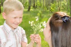 Der Junge gibt seiner Mutter Blumen Lizenzfreie Stockfotos