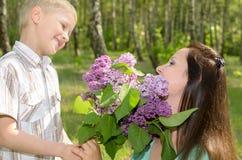 Der Junge gibt seiner Mutter Blumen Lizenzfreies Stockfoto