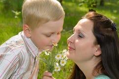 Der Junge gibt seiner Mutter Blumen Stockbild