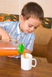 Der Junge gießt Saft in einem Becher Stockfotografie