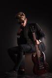 Der junge Gitarrist, der seine Jacke durch sie sitzt und hält, ist Kragen Lizenzfreie Stockbilder