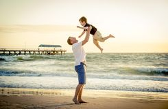 Der junge glückliche Vater, der in seinem hält, bewaffnet den kleinen Sohn, der ihn am Strand aufstellt Stockbild