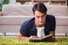 Der junge gutaussehende Mann, der mit weißem Kätzchen spielt lizenzfreies stockbild
