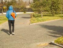 Der junge gutaussehende Mann, der einen Matrosen mit Sport trägt, bauschen sich und gehen in Park, hintere Ansicht Lizenzfreie Stockfotos