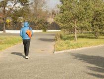 Der junge gutaussehende Mann, der einen Matrosen mit Sport trägt, bauschen sich und gehen in Park, hintere Ansicht Lizenzfreie Stockfotografie