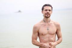 Der junge gutaussehende Mann gegen das Meer Das Kerllächeln und -blicke vorwärts Stockfotos