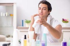 Der junge gutaussehende Mann im Badezimmer im Hygienekonzept stockfoto