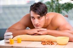 Der junge gutaussehende Mann während des Badekurortverfahrens Lizenzfreies Stockfoto