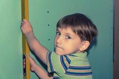 Der Junge hält das errichtende Niveau und überprüft die Genauigkeit der Wand stockfotografie