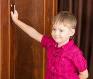 Der Junge hält den Griff der Garderobe Stockfotografie