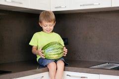 Der Junge hält eine große grüne Wassermelone stockfotos