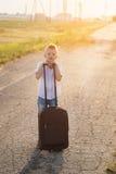 Der Junge hält einen Koffer an einem sonnigen Tag des Sommers Lizenzfreie Stockfotos