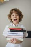 Der Junge hält einen Stapel Bücher Lizenzfreies Stockbild
