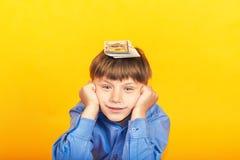 Der Junge hält Geld auf seinem Kopf, liegen Dollar auf dem child?s Kopf, aber er doesn?t kennt was, mit ihnen zu tun lizenzfreies stockbild