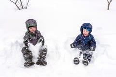 Der Junge hält Schnee in den Händen aktive Winterzeit draußen Lizenzfreies Stockfoto